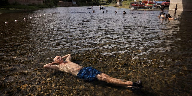Gerry Huddleston of Santa Rosa, Calf. cools off in the very shallow water of the Russian River, Wednesday, June 16, 2021 at the Veterans Memorial Beach in Healdsburg, Calif. An unusually early and long-lasting heat wave brought more triple-digit temperatures Wednesday to a large swath of the U.S. West, raising concerns that such extreme weather could become the new normal amid a decades-long drought. (Kent Porter/The Press Democrat via AP)