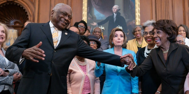 House Majority Whip James Clyburn, D-S.C., center left, reaches over to Rep. マキシンウォーターズ, D-Calif., joined by Speaker of the House Nancy Pelosi, D-Calif。, センター, and members of the Congressional Black Caucus. (AP Photo/J. Scott Applewhite)