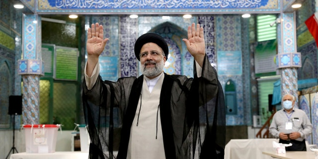 Ebrahim Raisi, a candidate in Iran's presidential elections waves to the media after casting his vote at a polling station in Tehran, Iran Friday, June 18, 2021. Iran began voting Friday in a presidential election tipped in the favor of a hard-line protege of Supreme Leader Ayatollah Ali Khamenei, fueling public apathy and sparking calls for a boycott in the Islamic Republic. (AP Photo/Ebrahim Noroozi)