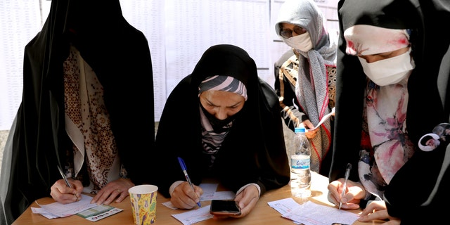 Voters fill out their ballot papers during the presidential election at a polling station in Tehran, Iran, Friday, June 18, 2021. Iranians voted Friday in a presidential election that a hard-line protege of Supreme Leader Ayatollah Ali Khamenei seemed likely to win, leading to low turnout fueled by apathy and calls for a boycott. (AP Photo/Ebrahim Noroozi)