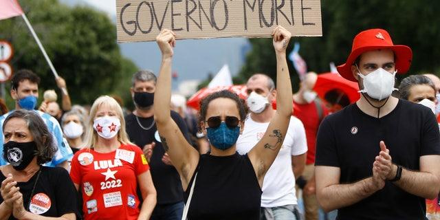 """Μια γυναίκα που φοράει προστατευτική μάσκα προσώπου και κρατάει μια πινακίδα με ανάγνωση μηνύματος στα Πορτογαλικά. """"500.000 κυβέρνηση θανάτου"""" Κατά τη διάρκεια διαμαρτυρίας εναντίον του προέδρου της Βραζιλίας Jair Bolsonaro για την αντιμετώπιση της πανδημίας και των οικονομικών πολιτικών του κοροναϊού, λένε ότι βλάπτουν τα συμφέροντα των φτωχών και της εργατικής τάξης, στο Ρίο ντε Τζανέιρο της Βραζιλίας, Σάββατο 19 Ιουνίου 2021. Η Βραζιλία πλησιάζει τον επίσημο θάνατο COVID-19 διόδια 500.000 - το δεύτερο υψηλότερο στον κόσμο.  (Φωτογραφία AP / Bruna Prado)"""