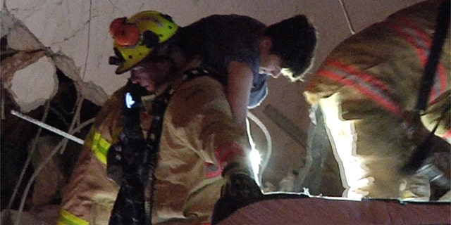 This photo taken from video provided by ReliableNewsMedia, firefighters rescue a survivor from the rubble of the Champlain Towers South Condo after the multistory building partially collapsed in Surfside, Fla., early Thursday, June 24, 2021.