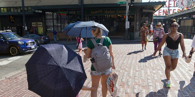 Sabina Ehmann and her daughter Vivian, visiting Seattle from North Carolina, are prepared with umbrellas to shield the sun during a heat wave hitting the Pacific Northwest, Sunday, June 27, 2021, in Seattle. (AP Photo/John Froschauer)