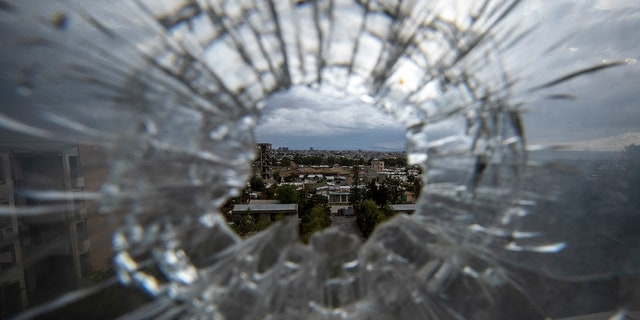 The city of Mekele is seen through a bullet hole in a stairway window of the Ayder Referral Hospital, in the Tigray region of northern Ethiopia on May 6, 2021.  (AP Photo/Ben Curtis, 文件)