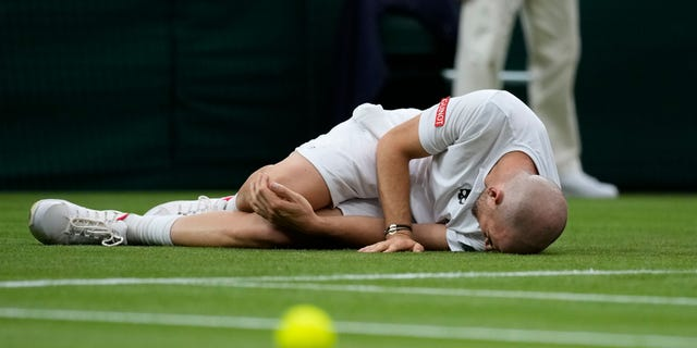 Adrian Mannarino of France lies on the ground in pain during the men's singles first-round match against Switzerland's Roger Federer on day two of the Wimbledon Tennis Championships in London, Tuesday June 29, 2021. (AP Photo/Kirsty Wigglesworth)