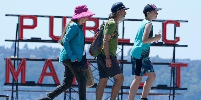 People walk near Pike Place Market, Tuesday, June 29, 2021, in Seattle. (AP Photo/Ted S. Warren)
