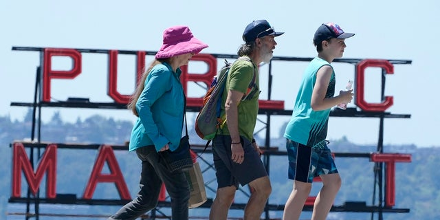 People walk near Pike Place Market, Tuesday, June 29, 2021, in Seattle. The unprecedented Northwest U.S. heat wave that slammed Seattle and Portland, Oregon, moved inland Tuesday — prompting an electrical utility in Spokane, Washington, to resume rolling blackouts amid heavy power demand. (AP Photo/Ted S. Warren)
