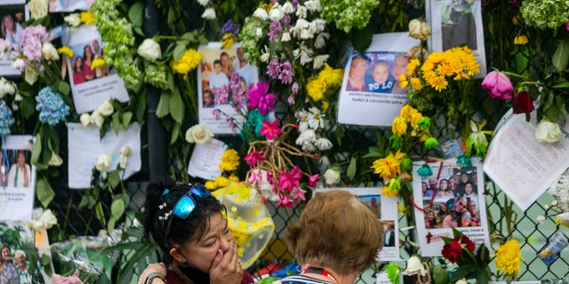 Mourners visit the makeshift memorial near the site of the collapsed condominium in Surfside, Fla., on Tuesday. (AP/Miami Herald)