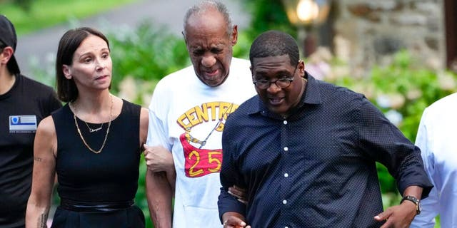 Bill Cosby, center, and spokesperson Andrew Wyatt, right, approach members of the media gathered outside Cosby's home in Elkins Park, Pa., Wednesday, June 30, 2021, after Pennsylvania's highest court overturned his sex assault conviction.