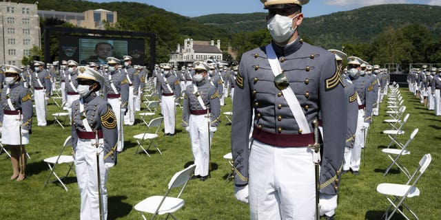 United States Military Academy graduating cadets wear face masks as they stand next to their socially-distanced seats during commencement ceremonies, Saturday, June 13, 2020, in West Point, N.Y. President Donald Trump's commencement speech to the 1,100 graduating cadets during a global pandemic comes as arguments rage over his threat to use American troops on U.S. soil to quell protests stemming from the killing of George Floyd by a Minneapolis police officer. (AP Photo/John Minchillo, Pool)