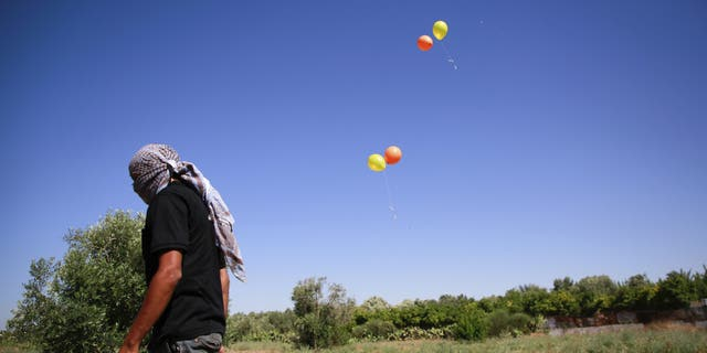 Masked Palestinian man walks away after launching incendiary balloons towards Israel. (Ahmed Zakot / SOPA Images/Sipa USA)(Sipa via AP Images)