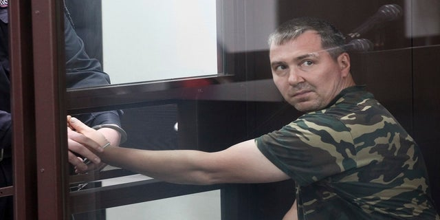 Alexander Popov, a man who was arrested on suspicion of murder sits behind the glass in a courtroom in the city of Gorodets, 36 miles northwest of Nizhny Novgorod, Russia, on Sunday. (AP)