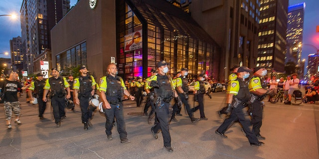 Police move around the Bell Centre, where thousands of Montreal Canadiens fans have assembled for Game 6 of an NHL hockey Stanley Cup semifinal playoff series against the Vegas Golden Knights, in Montreal, Thursday, June 24, 2021. Today is also the provincial holiday of Saint-Jean-Baptiste Day. (Peter McCabe/The Canadian Press via AP)
