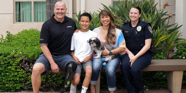 Chappie Hunter and his family found a dog that tugged at their heartstrings. They adopted Chloe, a 9-year-old Shih Tzu with double-amputated back legs. Pictured here are Chappie, Gavin and Arlene Hunter, Officer Boney and dog Chloe. (San Diego Humane Society)