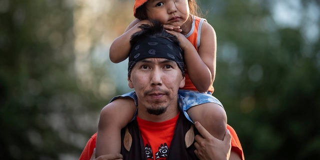 Cowichan Tribe member Benny George holds his child Bowie, 3, on his shoulders as they listen during a ceremony and vigil for the 215 children whose remains were found buried at the former Kamloops Indian Residential School, in Vancouver, British Columbia, on National Indigenous Peoples Day, Monday, June 21, 2021. (Darryl Dyck/The Canadian Press via AP)