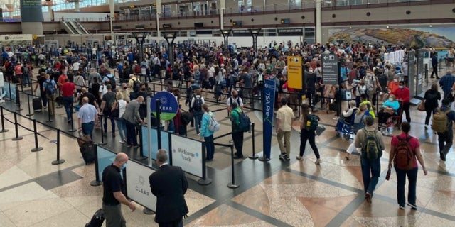 Travelers wait for a security check at Denver International Airport.