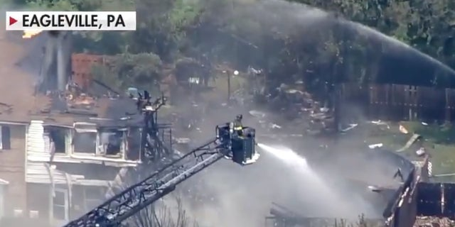Firefighters are battling a three-alarm fire that broke out after a series of explosions at a residential complex in Pennsylvania.  The body of a suspect involved in an armed conflict with police was later found at his home.