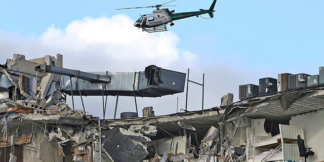A Miami-Dade Police helicopter flies over the Champlain Towers South Condo after the multistory building partially collapsed, Thursday, June 24, 2021, in Surfside, Florida.