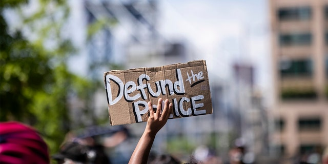"""A protester holds up a homemade sign that says, """"Defund the Police"""" with the Manhattan Bridge behind them as they perform a peaceful protest walk across the Brooklyn Bridge. (Photo by Ira L. Black/Corbis via Getty Images)"""