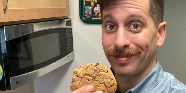 Thomas Frezza, a public affairs specialist for the Naval History and Heritage Command, is pictured with a chocolate chip cookie he made from the 1945 Navy Cookbook. (U.S. Navy Photo)