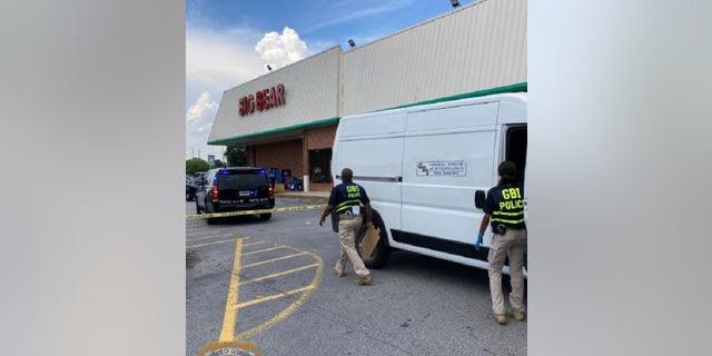Investigadores de la Oficina de Investigaciones de Georgia en el lugar de un tiroteo en un supermercado el lunes en el que murió un cajero y el presunto pistolero y un oficial de reserva resultaron heridos.
