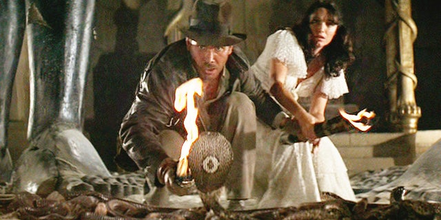 Seen here, Harrison Ford as Indiana Jones facing a cobra snake in the Well of the Souls chamber.  In the background is Karen Allen as Marion Ravenwood. The initial theatrical release was June 12, 1981.