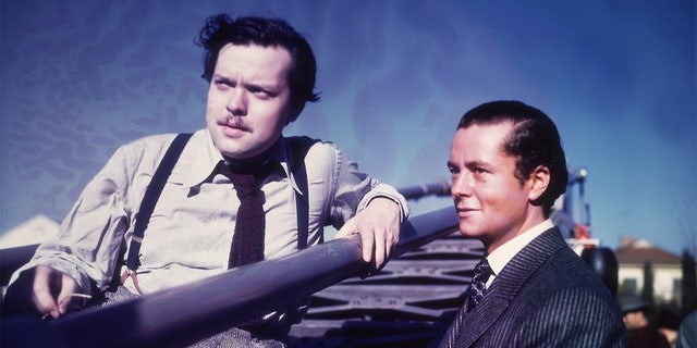 American actor, producer and director Orson Welles sits in a stadium while American actor Tim Holt stands next to him outdoors on the set of Welles' film, 'The Magnificent Ambersons'.