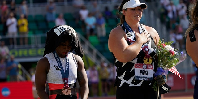 Gwendolyn Berry, left, drapes her Activist Athlete T-Shirt over her head as DeAnna Price stands for the national anthem after the finals of the women's hammer throw at the U.S. Olympic Track and Field Trials Saturday, June 26, 2021, in Eugene, Ore. Price won and Berry finished third. (AP Photo/Charlie Riedel)