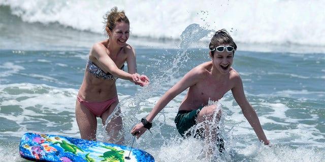 La gente juega en el agua en la playa de Santa Mónica el miércoles 16 de junio de 2021 en Santa Mónica, California.