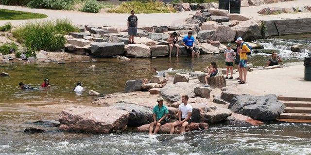 La gente se refresca en el agua en la confluencia del río South Platte y Cherry Creek en Denver el miércoles 16 de junio de 2021.