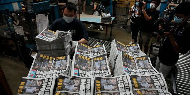 A worker packs copies of Apple Daily newspaper at the printing house in Hong Kong, early Friday, June 18, 2021.