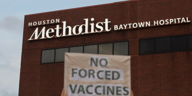 FILE - In this June 7, 2021, file photo, a person holds a sign to protest at Houston Methodist Hospital in Baytown, Texas, a policy that says hospital employees must get vaccinated against COVID-19 or lose their jobs. June 22, 2021. (Yi-Chin Lee/Houston Chronicle via AP, File)