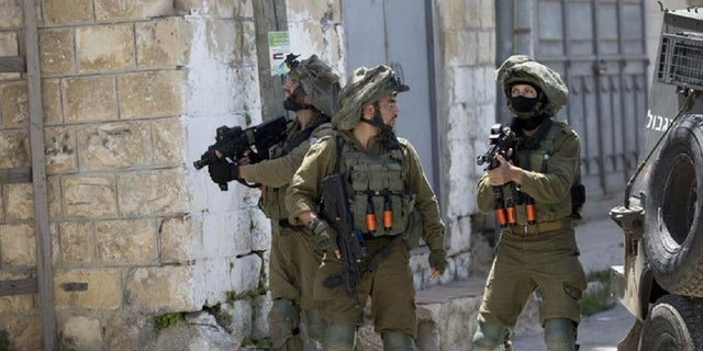 Israeli soldiers patrol after a soldier was killed when a rock thrown off a rooftop struck him in the head during an arrest raid, in the village of Yabad near the West Bank city of Jenin, in May 2020. The Israeli military says it is reining in a controversial practice of conducting late-night raids of Palestinian homes in the West Bank aimed at gathering information about the houses and their inhabitants.