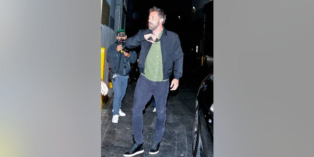 Ben Affleck attempted to hide his face from cameras with his cell phone while stepping out for dinner in Beverly Hills with JLo.