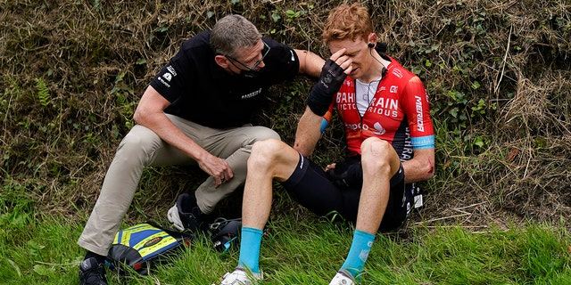 Australia's Jack Haig gets assistance from a team member after crashing during the third stage of the Tour de France cycling race over 113.65 miles with start in Lorient and finish in Pontivy, France, Monday, June 28, 2021. (AP Photo/Daniel Cole)