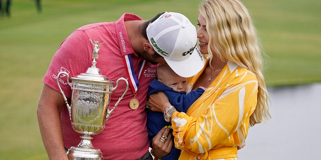 Jon Rahm, of Spain, holds the champions trophy for photographers as he stands with his wife, Kelley Rahm, and kisses their child, Kepa Rahm, 11 months, after the final round of the U.S. Open Golf Championship, Sunday, June 20, 2021, at Torrey Pines Golf Course in San Diego. (AP Photo/Marcio Jose Sanchez)