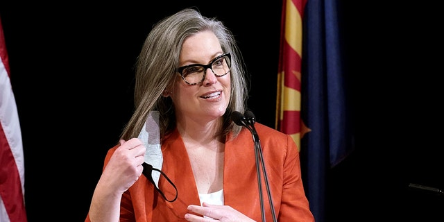 Arizona Secretary of State Katie Hobbs removes her face covering as she addresses the members of Arizona's Electoral College prior to them casting their votes in Phoenix, Ariz., on Dec. 14, 2020.