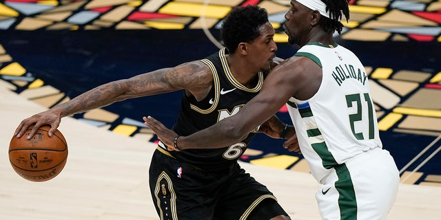 Atlanta Hawks 'Lou Williams (6) keeps the ball out of Milwaukee Bucks' Jrue Holiday (21) during the first half of the fourth game of the Eastern Conference NBA basketball playoff on Tuesday, June 29, 2021 in Atlanta.  (AP Photo / Brynn Anderson)