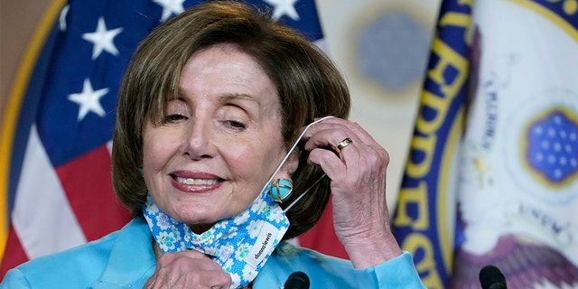 In this May 19, 2021, file photo House Speaker Nancy Pelosi takes off her face mask to talk to reporters on Capitol Hill in Washington, D.C.