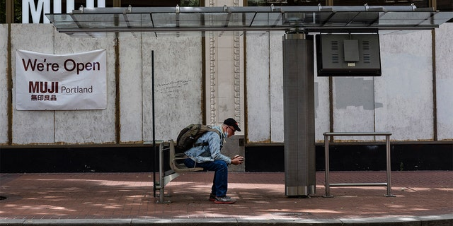 A man sits at a bus stop as wooden panels barricade shops because of on-going protests on Saturday, June 5, 2021 in downtown Portland, Ore. City officials insist Portland is resilient as they launch a revitalization plan — in the form of citywide cleanups of protest damage, aggressive encampment removals, increased homeless services and police reform — to repair its reputation.