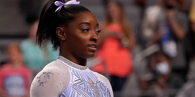 Simone Biles waits her turn to compete on the balance beam during the U.S. Gymnastics Championships, Friday, June 4, 2021, in Fort Worth, Texas. Biles wore a goat laced into her leotard during the competition. (AP Photo/Tony Gutierrez)