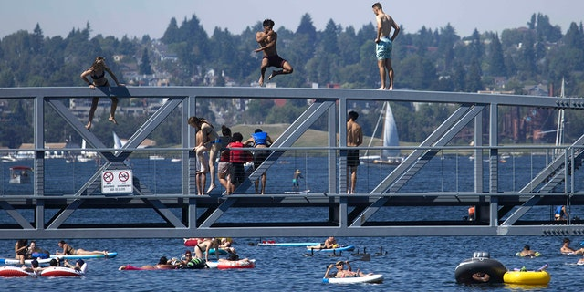 Two people jump from a pedestrian bridge at Lake Union Park into the water during a heat wave hitting the Pacific Northwest, Sunday, June 27, 2021, in Seattle. A day earlier, a record high was set for the day with more record highs expected today and Monday. (AP Photo/John Froschauer)