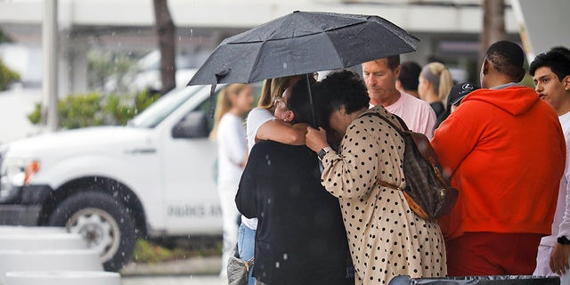 People embrace at the Surfside Community Center where authorities are taking residents and relatives from a partially collapsed building in Miami Beach, Florida, U.S., June 24, 2021.