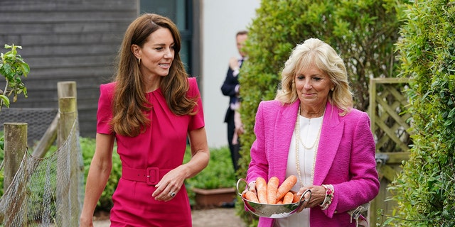 Britain's Kate, Duchess of Cambridge, left, and US First Lady Jill Biden, carrying carrots for the school rabbit, Storm, during a visit to Connor Downs Academy in Hayle, West Cornwall, during the G7 summit in England, Friday, June 11, 2021. (Aaron Chown/Pool photo via AP)