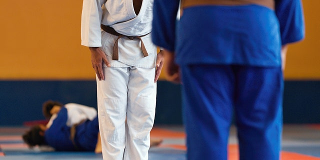 Two judo fighters or athletes greeting each other in a bow before practicing martial arts in the background of the ongoing match