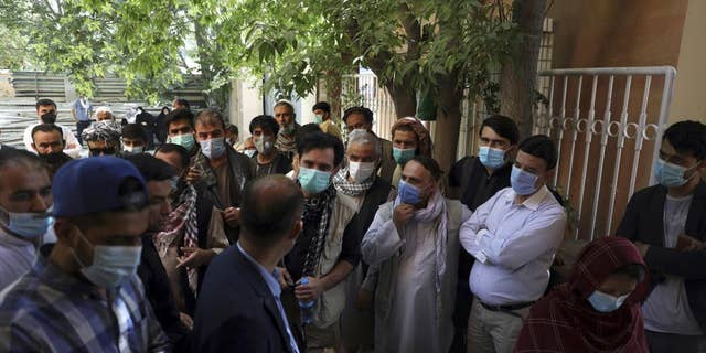 Residents, wearing face masks to help curb the spread of the coronavirus, line up to receive the Sinopharm COVID-19 vaccine at a vaccination center, in Kabul, Afghanistan, Wednesday, June 16, 2021.
