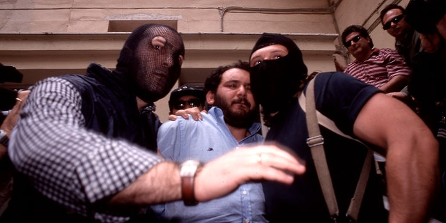 Giovanni Brusca, center, is seen during his capture in 1996. (Getty Images)