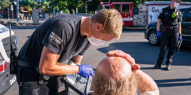 A paramedic with Falck Northwest ambulances treats a man experiencing heat exposure during a heat wave, Saturday, June 26, 2021, in Salem, Oregon. (AP Photo/Nathan Howard)