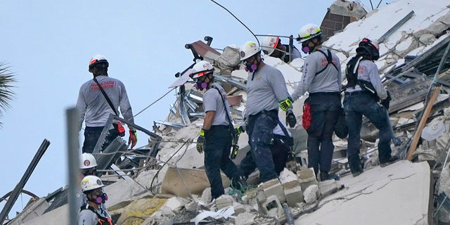 Rescue workers look through the rubble where a wing of a 12-story beachfront condo building collapsed, Thursday, June 24, 2021, in the Surfside area of Miami. (AP Photo/Lynne Sladky)