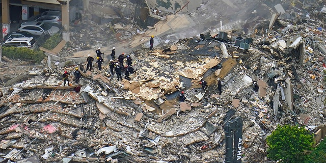 Rescue workers search in the rubble at the Champlain Towers South Condo, Friday, June 25, 2021, in Surfside, Fla. The seaside condominium tower collapsed on Thursday.